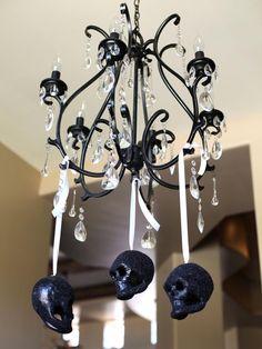 décoration d'Halloween avec des crânes noirs suspendus sur un ruban blanc