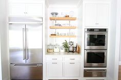 White Kitchen on twopeasandtheirpod.com The perfect white kitchen. with double ovens, two refrigerators, two dishwashers, two islands, two sinks, and open shelving.