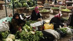 Women sell vegetables at a market in the Egyptian Delta town of Zagazig on 7 January 2013.