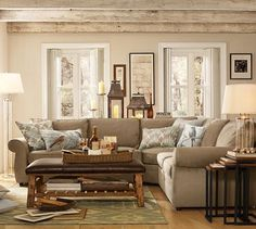 Livingroom with exposed wood beams, hardwood floors, tan sofa and pale blue accents.