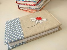 A6 embroidered daisy removable notebook cover and notebook    The notebook is made using a natural, cream coloured linen and cotton blend fabric, with a spotty blue and white linen blend on the bottom section. A cheerful blue spotted cotton is used for the inside of the cover. The daisy flower has been hand cut from a vintage sheet, layered on top of the linen and then embroidered using free-motion machine embroidery. The cover is fully removable - once the notebook is full, you can easily…