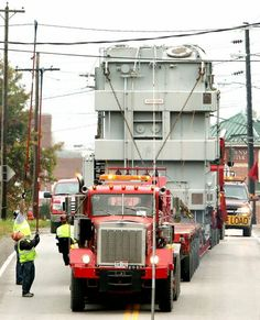 workers move wires, lights, and poles to transport a 340-ton power  transformer