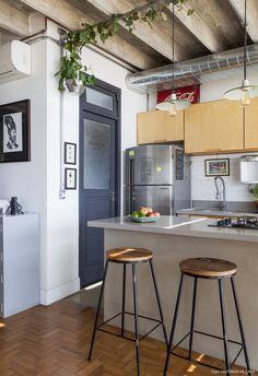 Cozinha tem estilo industrial e marcenaria com madeira clara.
