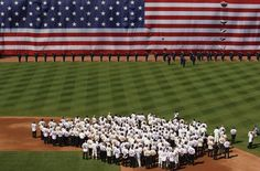 Former Red Sox players and managers stand at second base and salute the flag during the pre-game ceremony as Fenway Park commemorates its 100th year anniversary before the start of American League MLB baseball action between the Boston Red Sox and New York Yankees at Fenway Park in Boston, Massachusetts April 20, 2012. REUTERS/Jessica Rinaldi (UNITED STATES - Tags: SPORT BASEBALL)
