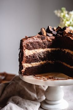 Super moist vegan chocolate peanut butter cake made with layers of tender and rich chocolate cake between irresistible peanut butter buttercream frosting and decadent chocolate buttercream frosting. No one will know this cake is vegan nor dairy free! #vegandessert #chocolatecake #peanutbutter #vegan