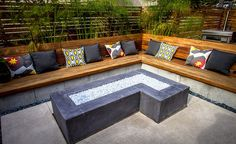 Here a concrete fire pit is pictured with built-in bench seating made of cumaru wood. Throw pillows have been added to give splashes of color. Behind the seating area are tall modern grasses used to soften the screen area in the back. Built In Seating, Built In Bench, Patio Seating, Garden Seating, Fire Pit Backyard, Backyard Patio, Backyard Landscaping, Backyard Ideas, Wedding Backyard