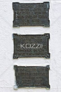 three metal plaque arranged in a row. - Close-up image of three metal plaque arranged over white wall.