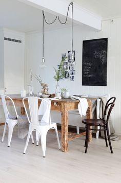 comedor en la cocina con pizarra en las lámparas de pared y colgantes encima de la mesa