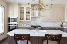 Creamy upper cabinets contrast against soft brown lower cabinets and island in this transitional kitchen. White-and-gray marble is used for the countertops and backsplash, evoking elegance and classic style.