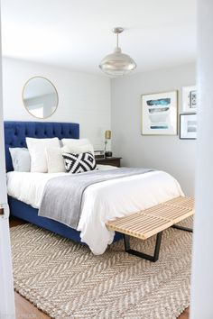 Add a bench to the end of your bed for a stylish spot to sit down. Love this wood bench paired with the white duvet cover and navy headboard. Such a pretty look for this master bedroom space. Wall Color is Valspar Filtered Shade