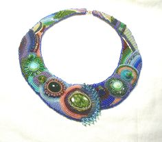 Rock Star Bead Embroidered Neckpiece $1,375    For this neckpiece, I chose the most richly jewel-colored beads in my rainbow trove – emerald, sapphire, garnet, peridot, opal, amethyst, and more. I also used pinks, greens and blues galore. The center focal stone seems to be granite, but all the other beads are glass. The beads encrust several sandwiched layers of nonwoven materials. I edged the neckpiece with cobalt and purple seed beads. I made the hook and eye clasp from gold-filled wire.