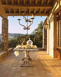 Architect Wayne Leong based the design of this Napa Valley guesthouse on rural Provence structures. The loggia's stone columns were constructed with stones excavated from the site. The 10-foot-long 17th-century table is cast iron and slate. Antique French bottles are from Vintage Home. The iron chandelier is from Formations.