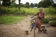 Suor Angélique sorride sulla sua bicicletta. Ogni giorno percorre grandi distanze in bici per monitorare l'evoluzione dei progetti che segue e fare visita alle donne che aiuta. www.unhcr.it UNHCR/B. Sokol