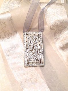 """Upcycled Vintage Necklace by NorthCoastCottage, $39.00. This vintage baroque/art nouveau piece c. 1920s was likely once a silver belt or shoe buckle. Here it's been upcycled or recycled as a necklace on a shimmering silver ribbon. Pendant 1.25""""w x 2.25"""" l. Adj. ribbon goes short or long."""