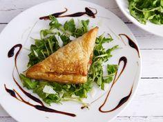 Belgian endive puff pastry triangles with arugula, Grana Padano flakes and pomegranate balsamic cream