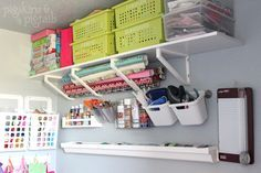 Shelf bracket to hold wrapping paper, plastic rain gutter for ribbons, white IKEA trashbin for loose ribbons