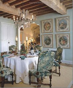 The dining room with a crystal chandelier.  I love the fancy chandelier next to the rough beams on the ceiling.  Notice the bar through the arched door. Ginny, the owner framed pieces of wallpaper to hang on the walls.