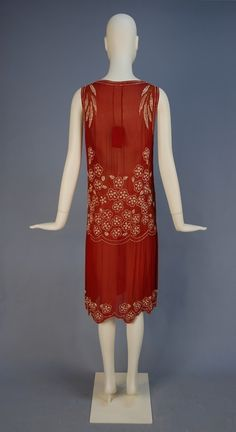 DECO BEADED CHIFFON DRESS. Sleeveless cranberry silk decorated in iridescent white and red beaded floral, having scalloped low waist with long, wide chiffon fringe, slightly gathered skirt with scalloped hem. Back