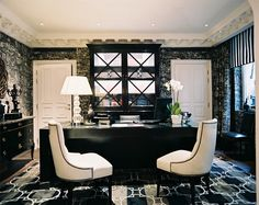 Area Rug Photo - A pair of upholstered chairs beside a black desk in an office filled with patterns