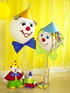 1. Auf Luftballons mit wasserfesten Stiften Gesichter malen.2. Kreppband mit einer Zackenschere schneiden, in der Mitte mit Geschenkband