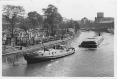 """Captioned: """"Two tugs, each pulling a barge. They are passing the  Kensal Green Gasworks on the right of the picture; and Kensal Green Cemetery on the left of the picture. The barges are going to Celotex.""""  #london #canal #tug #barge #kensal #green paddington #arm #celotex #gasworks #british #waterways"""