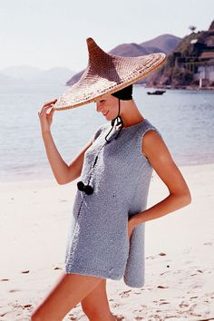 1964  A model wears an oversize straw hat and coverup on the beach.