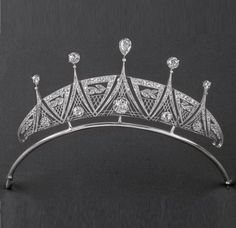 An interesting Art Deco diamond tiara, circa 1920, featuring multiple panels with internal lattices and laurel leaf motifs. Five large circular diamonds within the main body of the piece and four more above it, with a central pear-shaped diamond