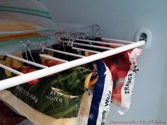 Use every inch of freezer space by clipping bags underneath the shelf. You'll not only gain space, but items won't be hidden underneath other items.