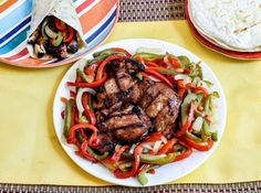 Onions, peppers and grilled chicken on a plate with a fajita and rice.