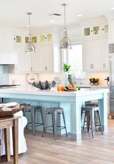 Beach style coastal kitchen with blue kitchen island and white cabinets