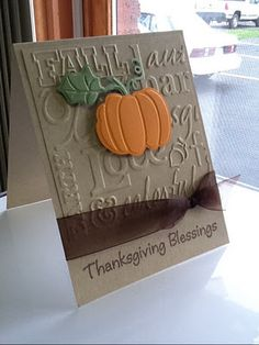 handmade Thanksgiving card ... kraft base ... Fall words embossing folder texture ... die cut and embossed pumpkin ... like the knotted ribbon hiding the line between embossed panel and card base ... great card!!