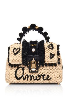 This **Dolce & Gabbana** bag is rendered in raffia and features a crochet handle and ayers trim.