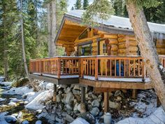 A log cabin with a deck over a stream