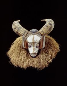 Africa | Tsekedi face mask from the Yaka people of Popokabaka, Kwango, Bandundu, DR Congo | wood, raffia, pigment, vegetal fibre, textile | ca. prior to 1931 | Although worn by young circumcised males at the end of the mukanda ritual, these masks have little importance and are only rarely seen during the grand dance performed by the young men in the surrounding villages.