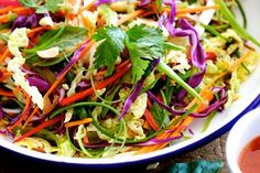 The 'slaw that makes salad hot  500g Chinese cabbage    75g small red cabbage    100g carrot, peeled    3 green (spring) onions    100g snow peas    1 red chilli    1 cup coriander sprigs    1 cup mint leaves    1 cup Asian basil leaves    2 tsp soft brown sugar    2 tbsp rice vinegar    2 tbsp fish sauce or soy sauce    1 tsp sesame oil    1 tbsp sweet chilli sauce    2 tbsp extra-virgin olive oil    sea salt and pepper
