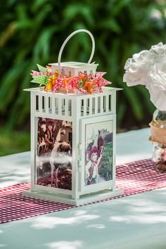 """Lanterns from Ikea. We put our childhood pictures in them, and strung a crane """"lei"""" around the top to give it some color."""