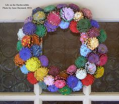 """""""Zinnia"""" Pine Cone Wreath.  Pine cones painted with acrylic paint and foam brushes and wire wrapped onto an 8"""" wire wreath.  Be sure to bake the pine cones before painting to kill off any critters.  You'll also need sturdy pruners to cut off the top 3/4 of the pine cone, floral wire, wire cutters, needle nose pliers and patience!"""