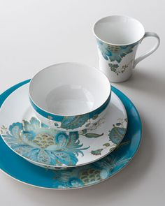 Pretty china dinnerware mixes artful florals with solid borders in a bold theme of teal. Includes four four-piece place settings.