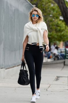 Gigi Hadid goes for a sport look with zipper moto leggings by Blue Life Fit, a white crop top, tennis shoes, and a knit sweater loosely tied around her shoulder.