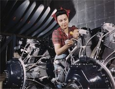 Woman working on an airplane motor at North American Aviation in California. Photographed by Alfred T. Palmer in June 1942.