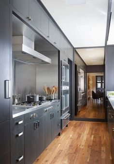 The couple's galley kitchen features stained ebonized wood cabinets, stainless-steel counters, a Gaggenau stove, and Amish hand-scraped walnut floors | archdigest.com