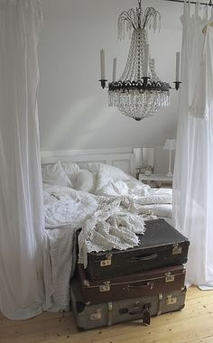 white bedroom, vintage luggage, chandelier