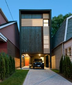 11 Small Modern House Designs // This narrow house fits tightly between the two houses on either side of it and makes up for it's narrow width by being slightly taller than the other houses around it.