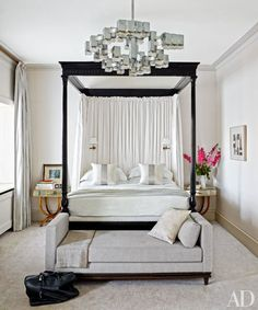 A luxe master bedroom featuring a four poster bed and a 1970s light fixture   archdigest.com