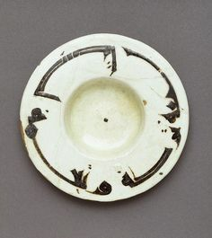 Small earthenware dish with inscription in black slip, Eastern Iran or Uzbekistan, 900-1000. Diameter: 11.2 cm, Height: 1.6 cm. C.47-1964: Given in memory of Arthur Lane; C.909-1935. Victoria & Albert Museum © V Images