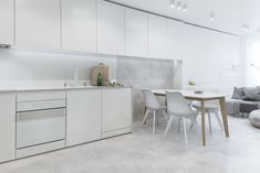 White appliances by Karim Rashid for Gorenje pair with concrete floors in the apartment's kitchen. Photo 2 of 6 in A Bright Palette Makes This Bulgarian Apartment Feel Bigger Than Its 600 Square Feet. Browse inspirational photos of modern homes.
