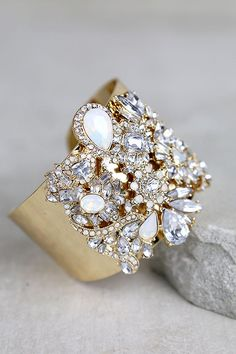 """Lulus Exclusive! The moment has arrived for the Dreamt of This Gold Rhinestone Cuff Bracelet to shine alongside your new stunning dress! A sturdy, and shiny, gold cuff bracelet is bedecked in clear and iridescent rhinestones. Bracelet has a 2.5"""" diameter."""