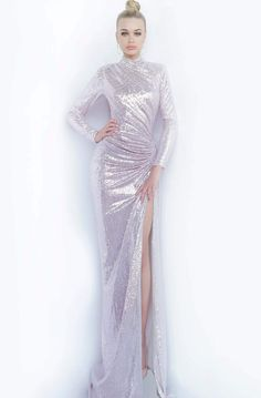Make your gorgeous grand entrance in this ravishing Jovani 1707 Prom Dress. This long form fitting ensemble is tailored in stretch metallic fabric and boast long slender sleeves and high closed neckline. Asymmetric ruching gathers along one side of the waist leading to the long fitted skirt that continues with a sexy high side slit. This classic beauty from Jovani fashion will finish off your attention-grabbing look for that special evening. Style: jovani_1707 Details: Stretch Metallic fabric, C Evening Gowns Couture, Long Evening Gowns, Formal Evening Dresses, Formal Dress, Metallic Prom Dresses, Metallic Dress, Sparkly Dresses, Metallic Fashion, Sequin Dress