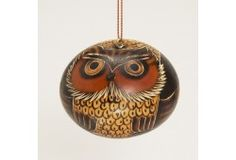 Thoughtful round owl ornament is made from an etched gourd. Artisans working with Manos Amigas in Lima, Peru, carve the design, after which they accent it with red-hot pieces of burned wood. The gourd is then painted with a natural paint made from ground chalk mixed with water. Later most of the finish is washed off; the residue gives beauty to the carved parts of the design. Decorative only. Keep out of reach of children.      Etched gourd     Assorted sizes     Made in Peru