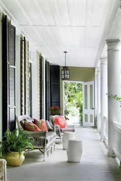 On this covered front porch, classic white wicker is dressed with zesty pillows, while classic black trim tempers the olive green paneled exterior.